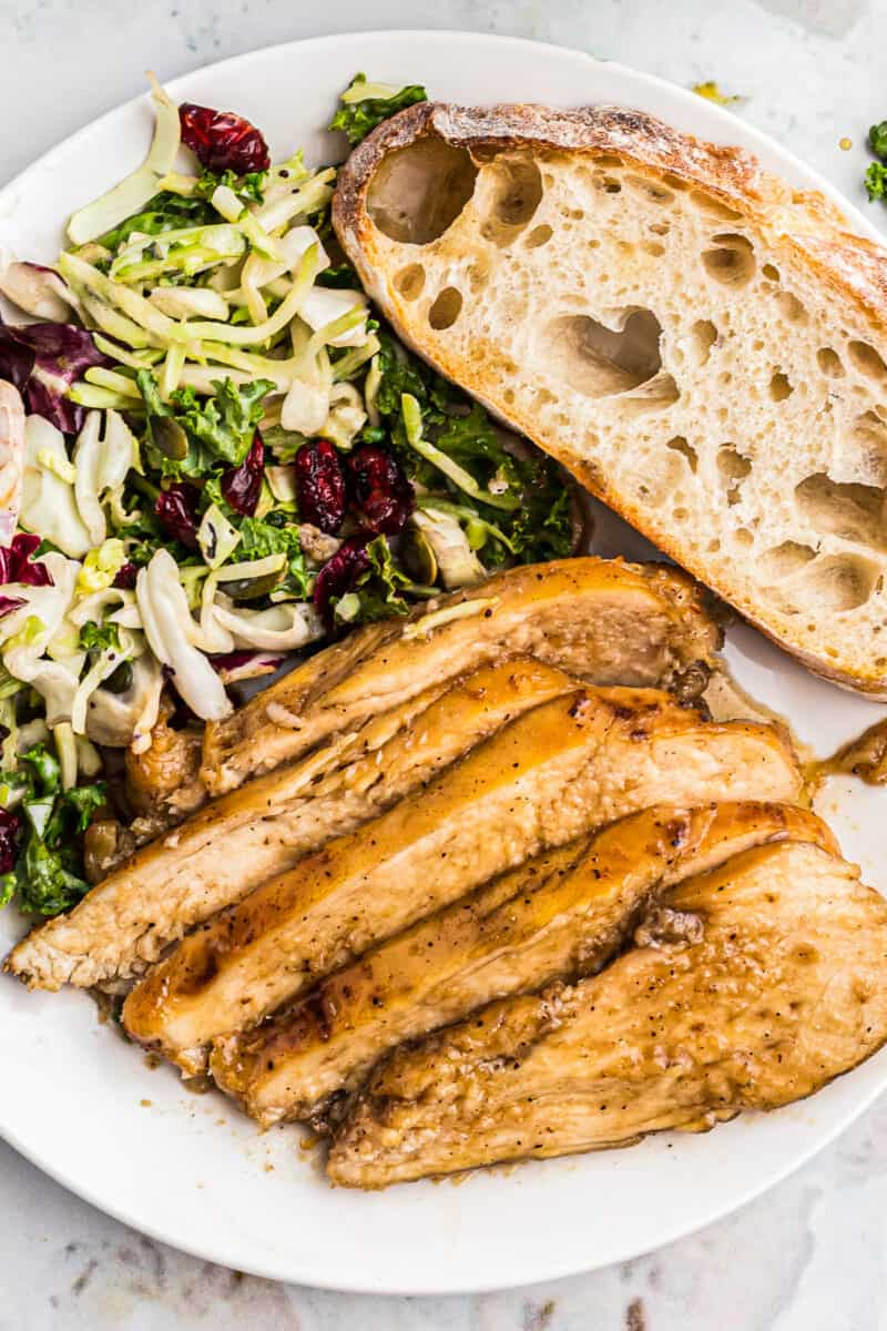 sliced bourbon chicken breast with bread and salad on plate