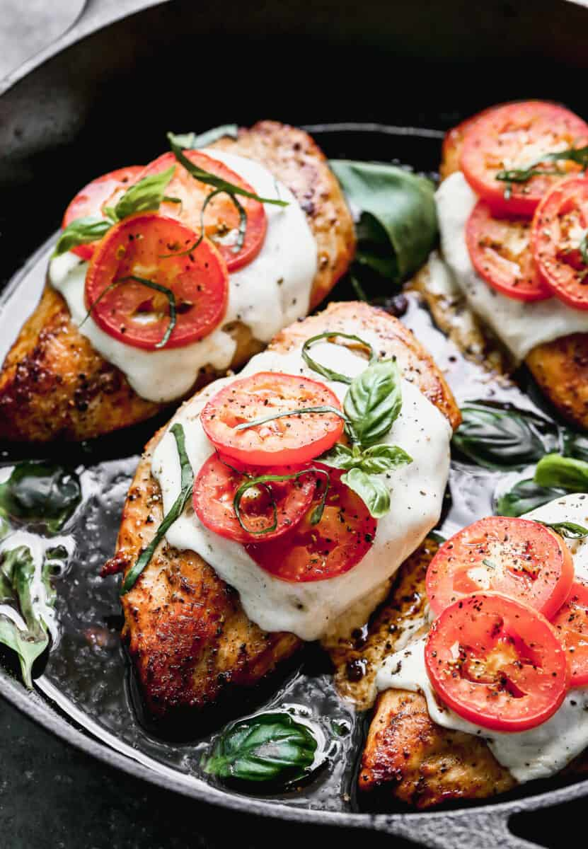 chicken topped with mozzarella basil and tomato in skillet