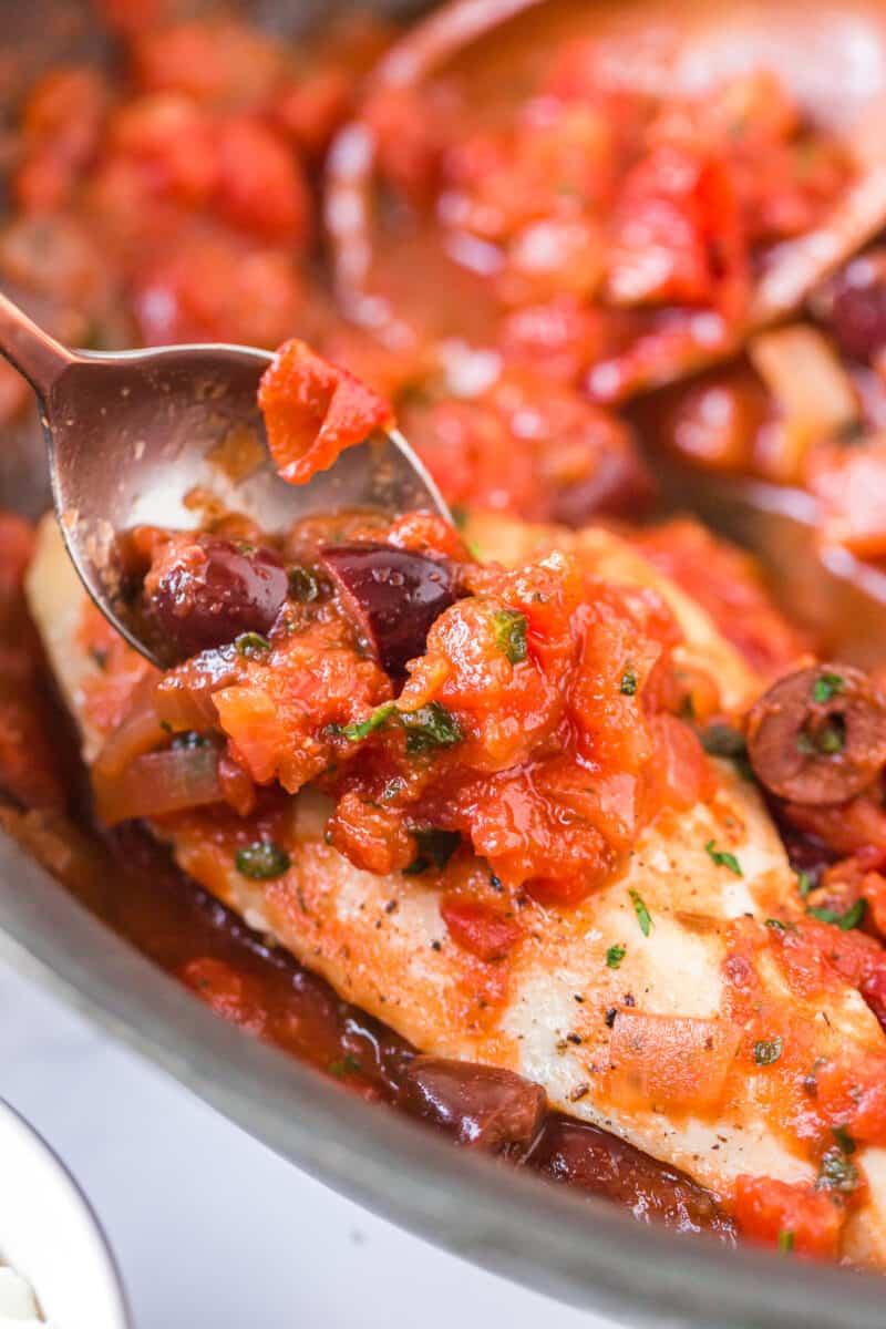 spooning sauce over mediterranean chicken