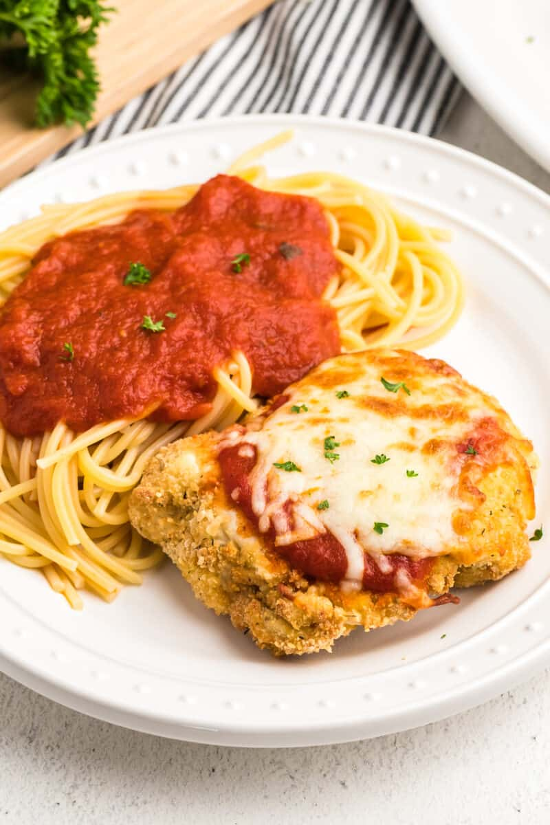 white plate with air fryer chicken parmesan with pasta