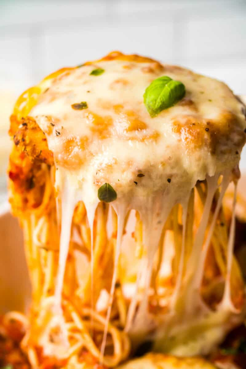 lifting up chicken parmesan with spaghetti in baking dish