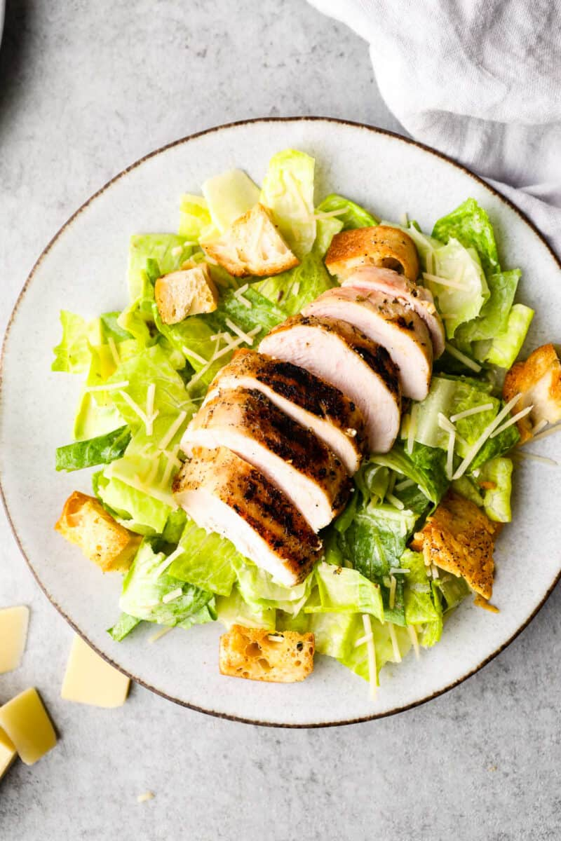 overhead image of grilled chicken caesar salad on white plate