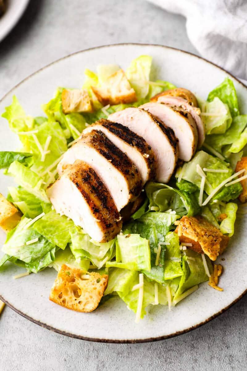 sliced grilled chicken on salad
