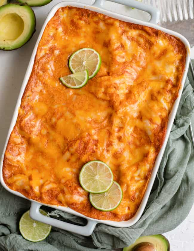 chicken enchilada casserole in baking dish with lime slices
