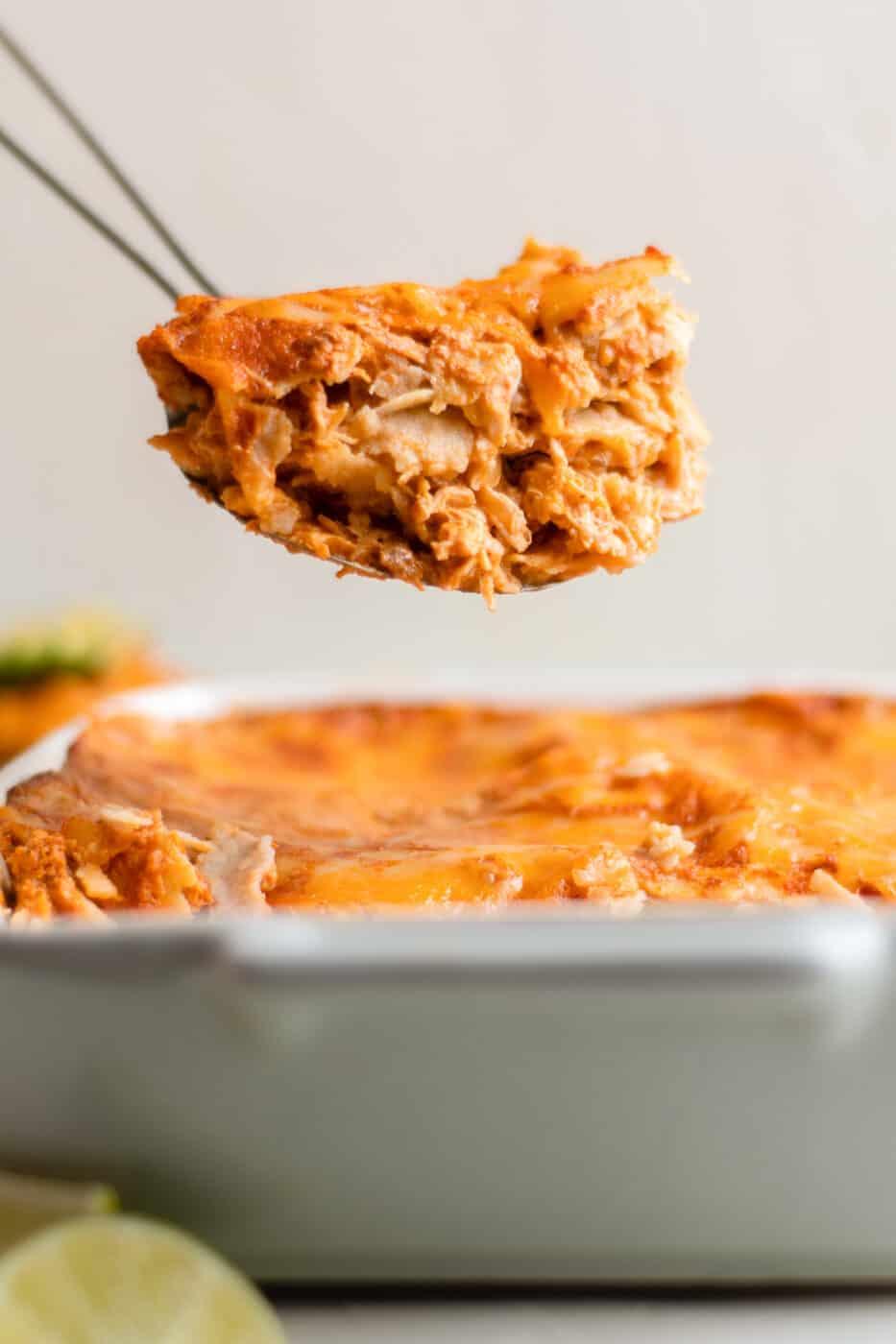 lifting up slice of enchilada casserole