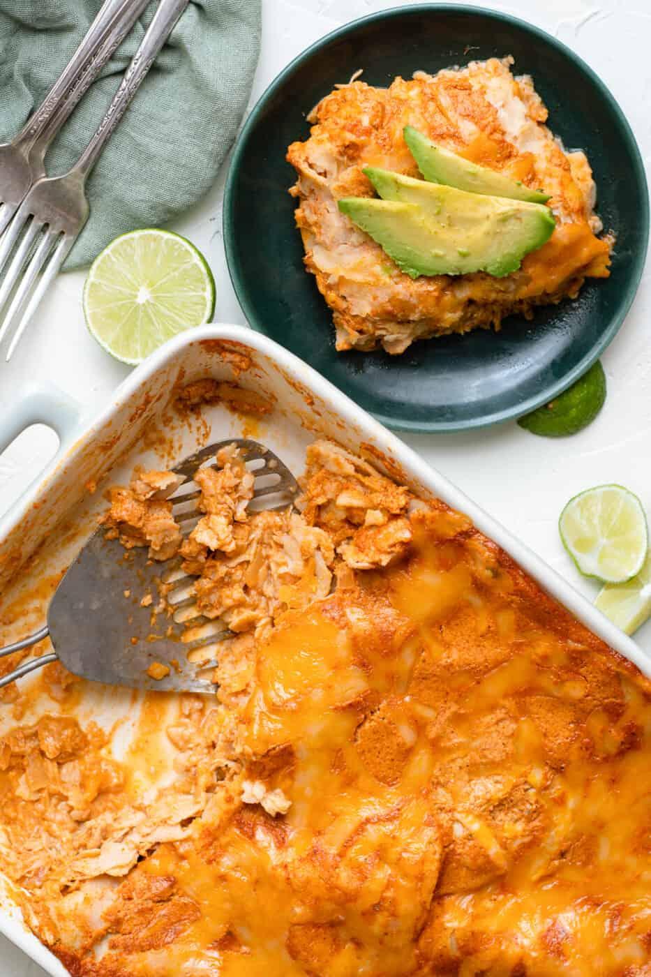 pan of chicken enchilada casserole next to plate