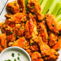 buffalo wings on white platter with dip