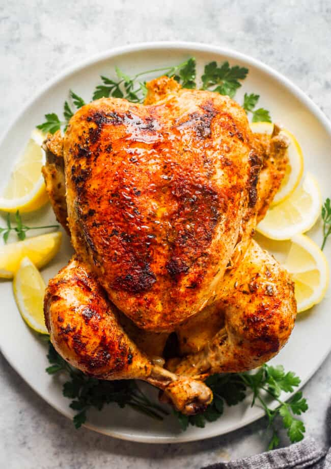 seasoned whole chicken with lemon on white plate