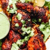 up close image of spiced peruvian chicken drizzled with green sauce