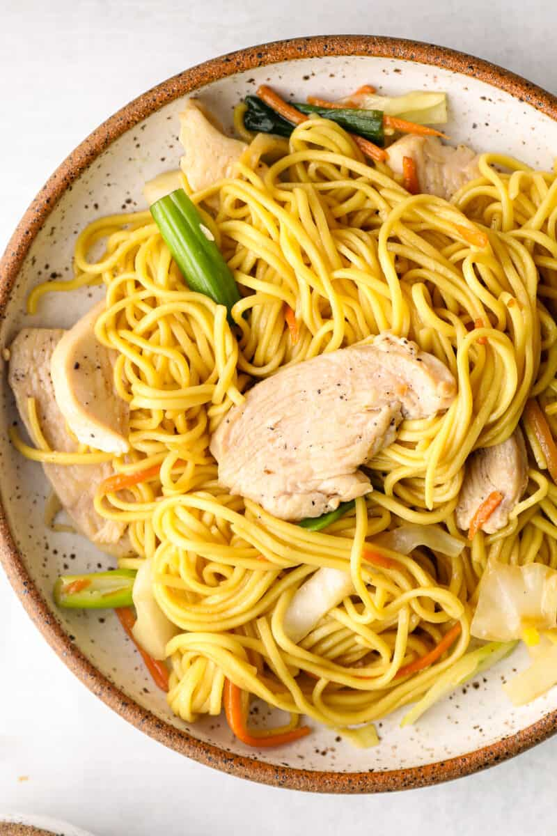 white plate with chicken chow mein noodles