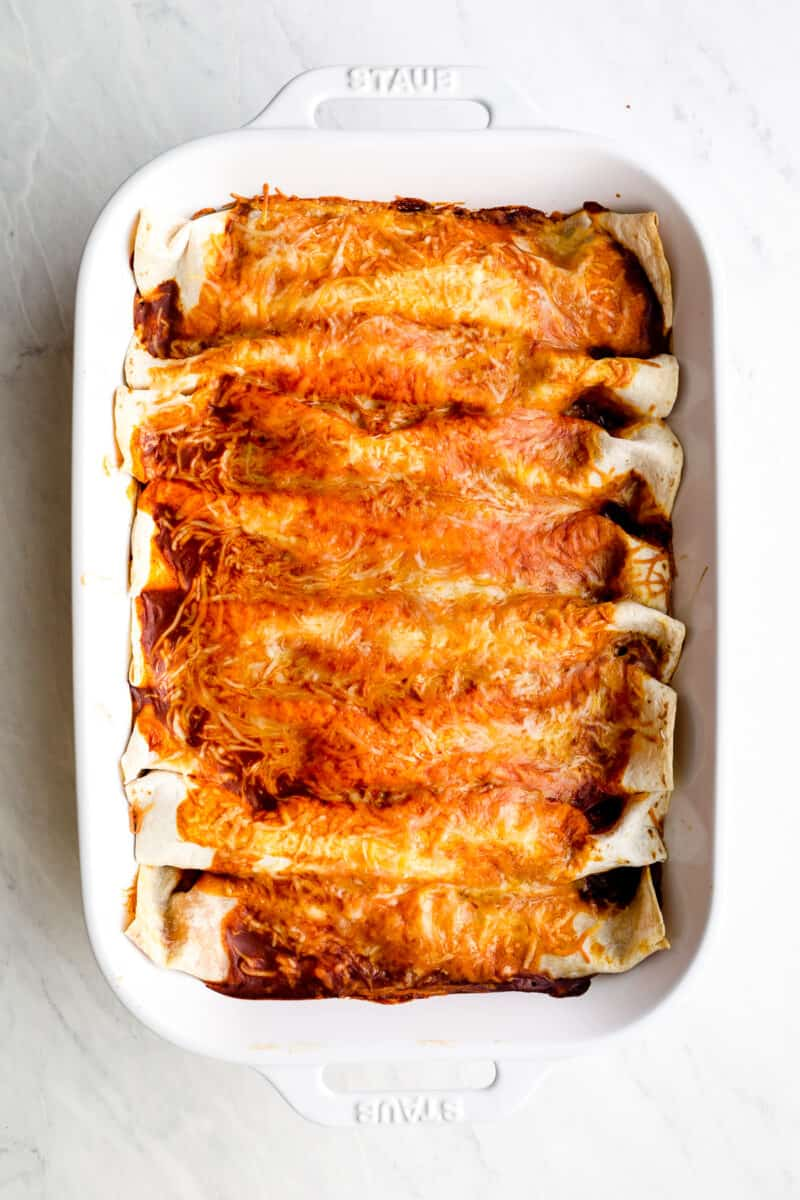 Chicken enchiladas with sauce.