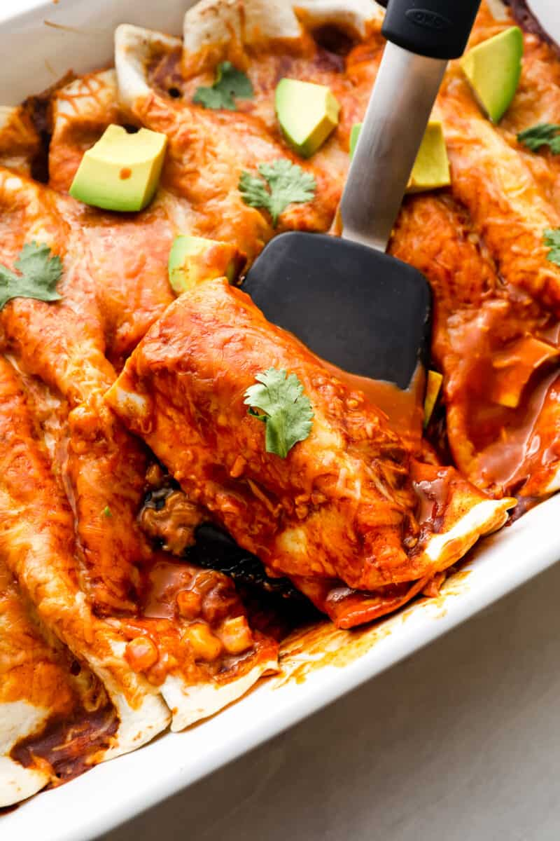 Lifting up red chicken enchilada.