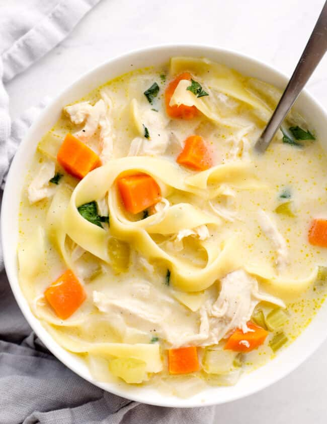 up close bowl of creamy chicken noodle soup with napkin