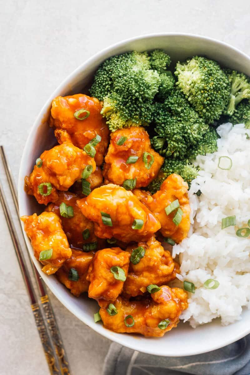 white bowl with crispy orange chicken, broccoli, and rice