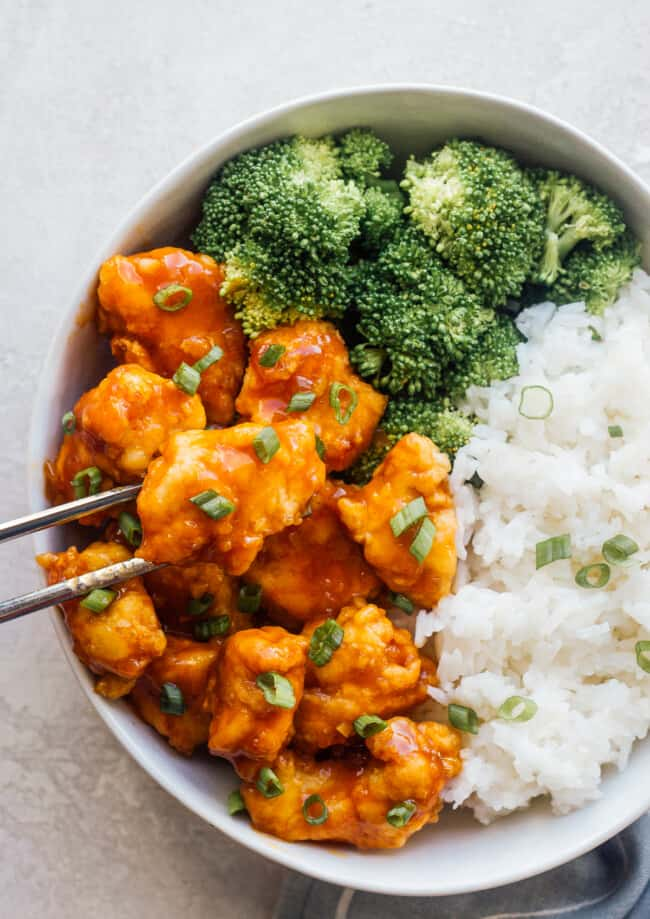bowl with orange chicken and rice with chopsticks