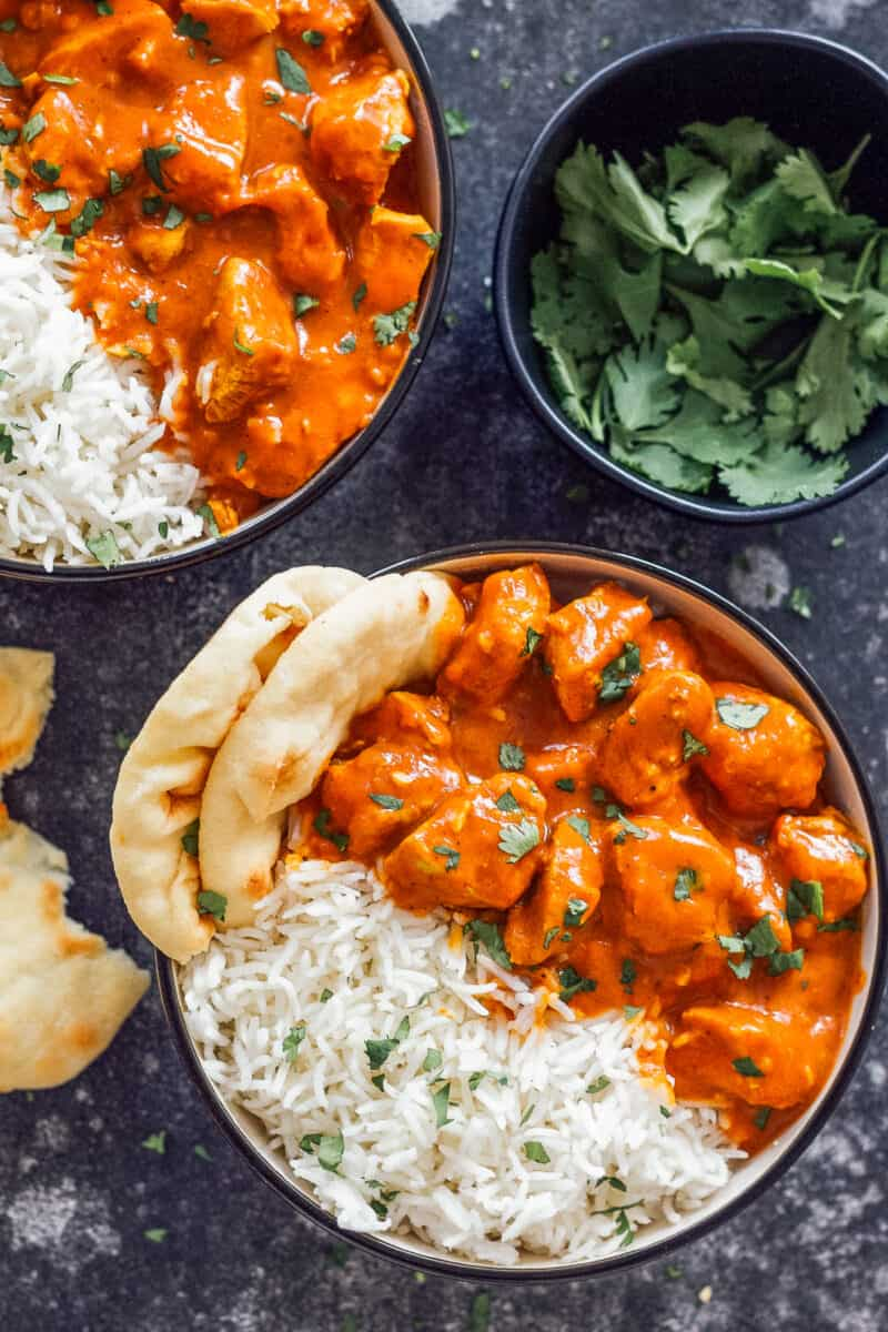 Two bowls of instant pot chicken tikka masala with rice and naan.