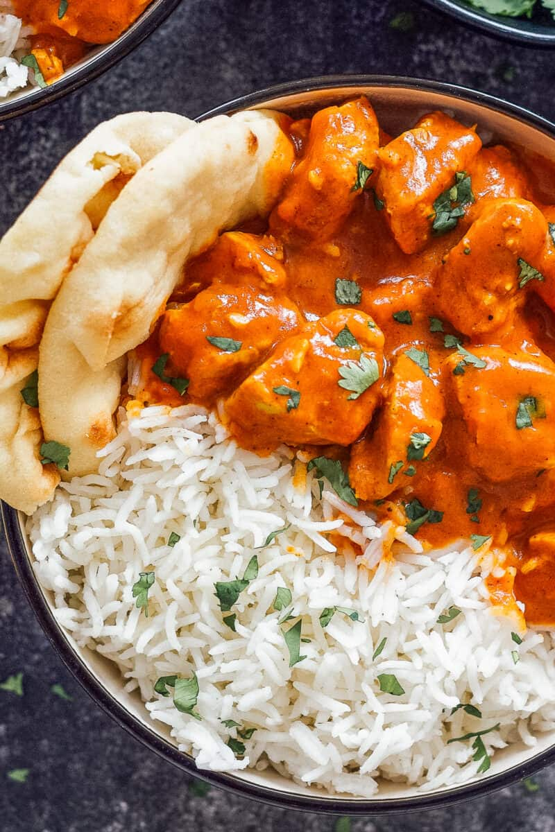 Up close image of bowl of chicken tikka masala with rice.