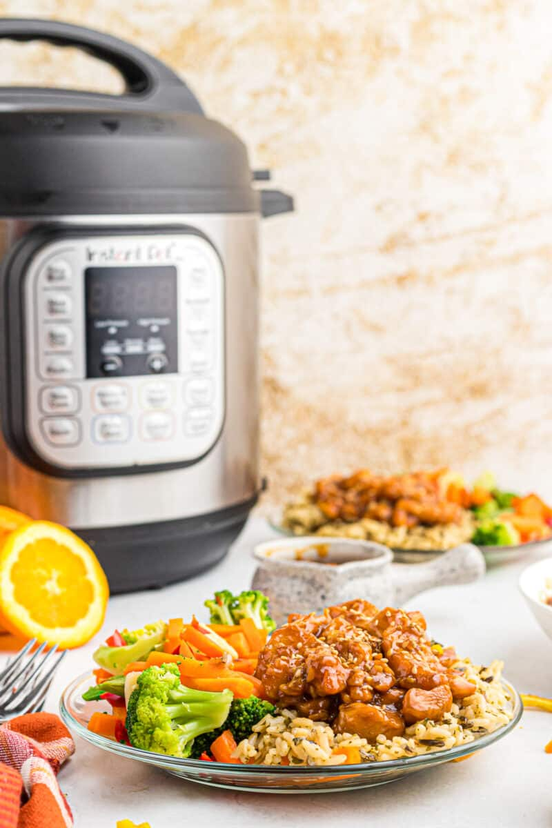 two plates of orange chicken next to instant pot