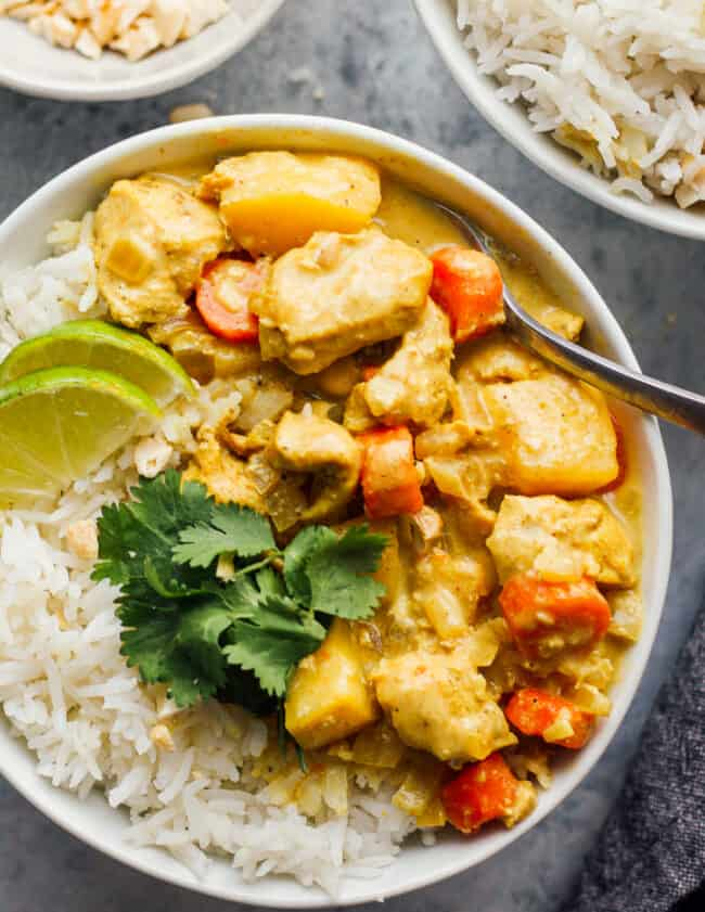crockpot yellow chicken curry with rice in white bowl