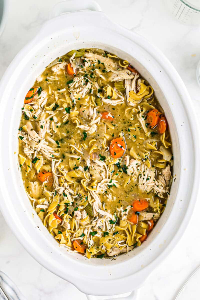 chicken noodle soup in a white crockpot
