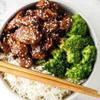crockpot sesame chicken with broccoli and rice in white bowl