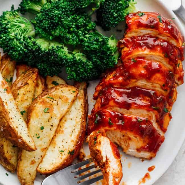 sliced bbq chicken breast on plate with broccoli and potato wedges