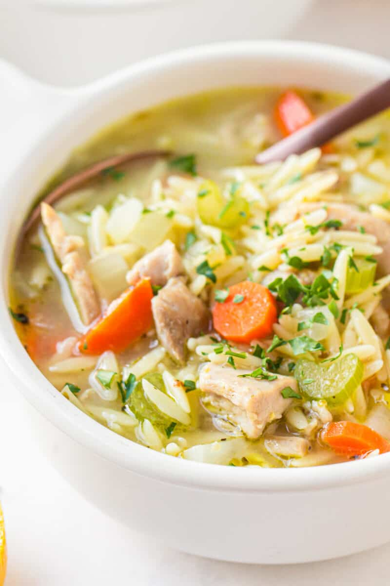 up close lemon orzo chicken soup with spoon