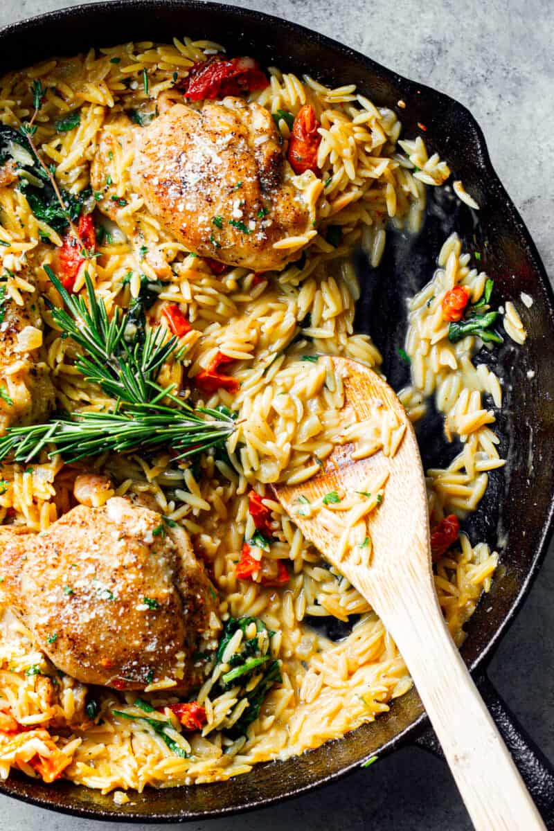 tuscan chicken or orzo in black skillet with wooden spoon