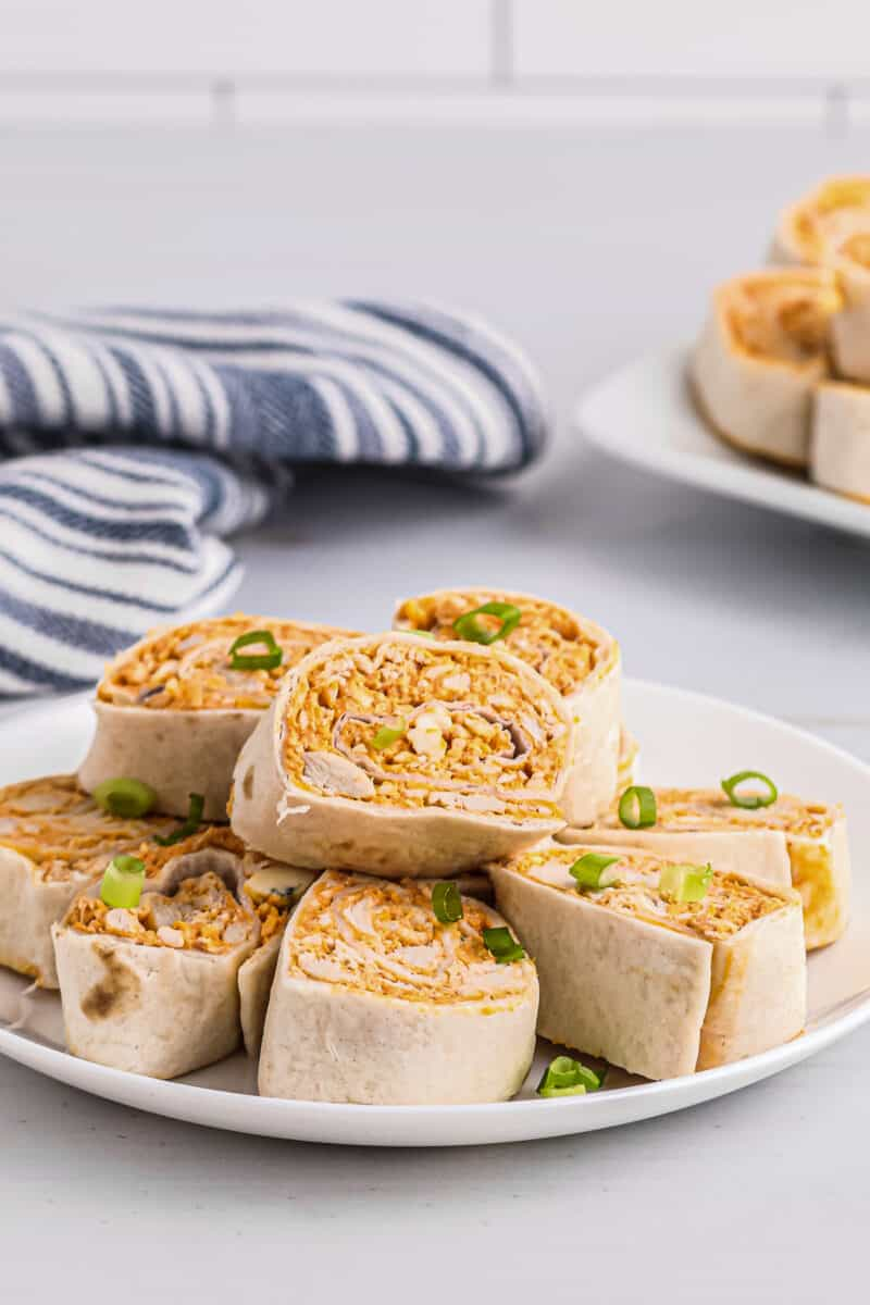 buffalo chicken roll ups stacked on white plate
