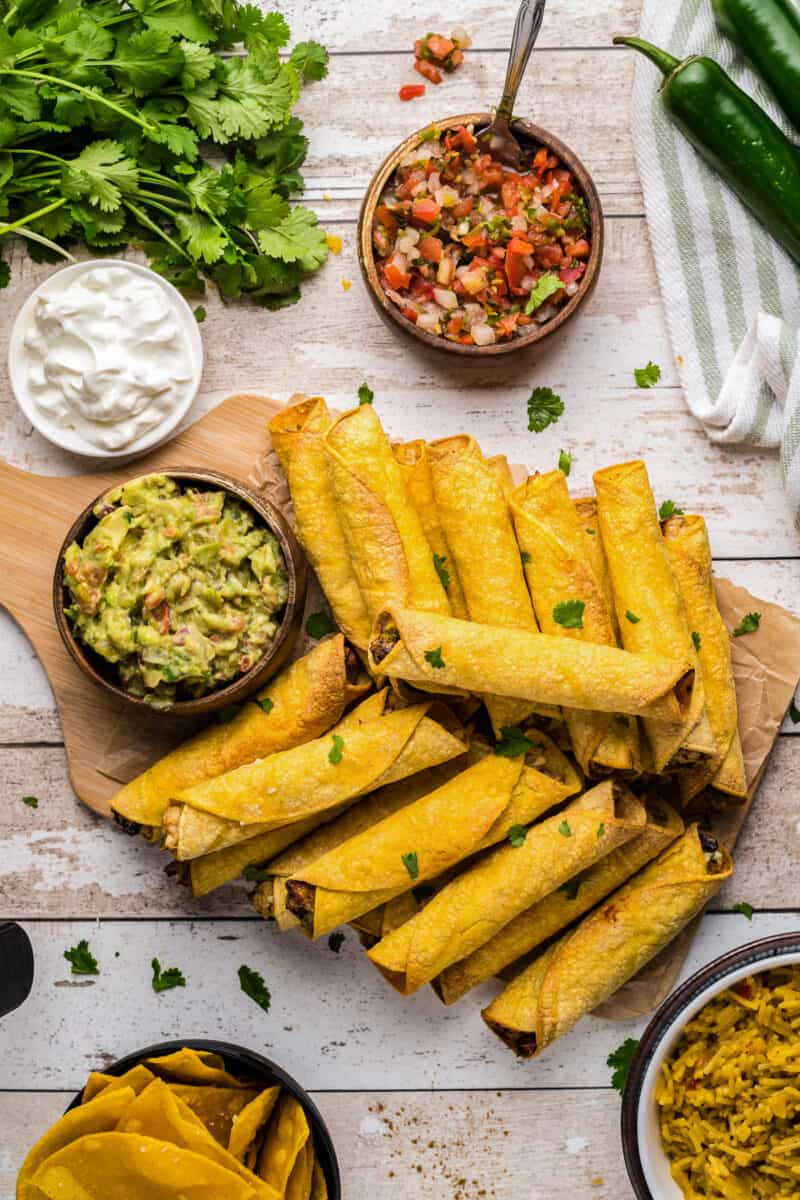 air fryer chicken taquitos on cutting board next to salsas and sour cream