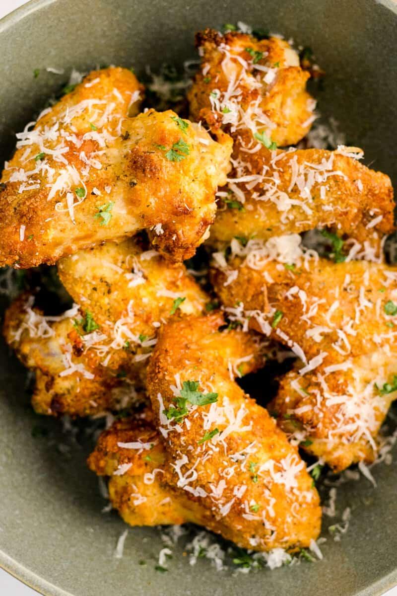 up close bowl of garlic parmesan wings in an air fryer