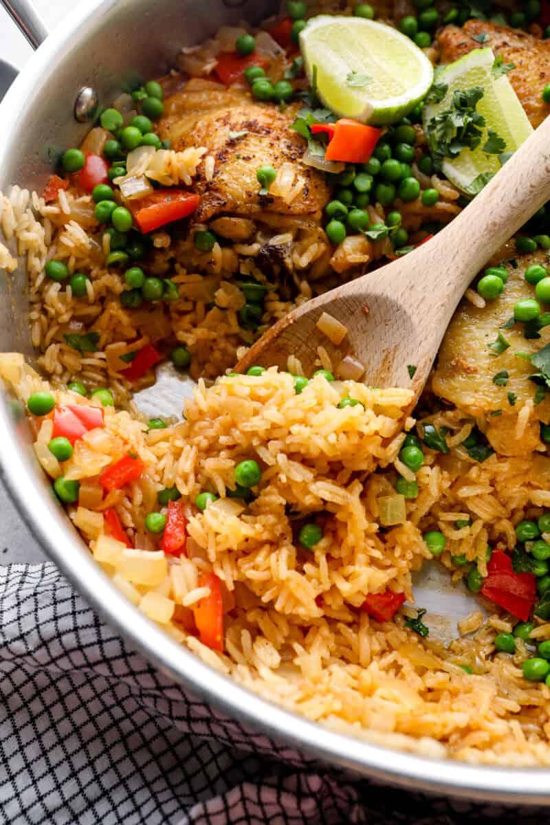 digging into arroz con pollo with wooden spoon