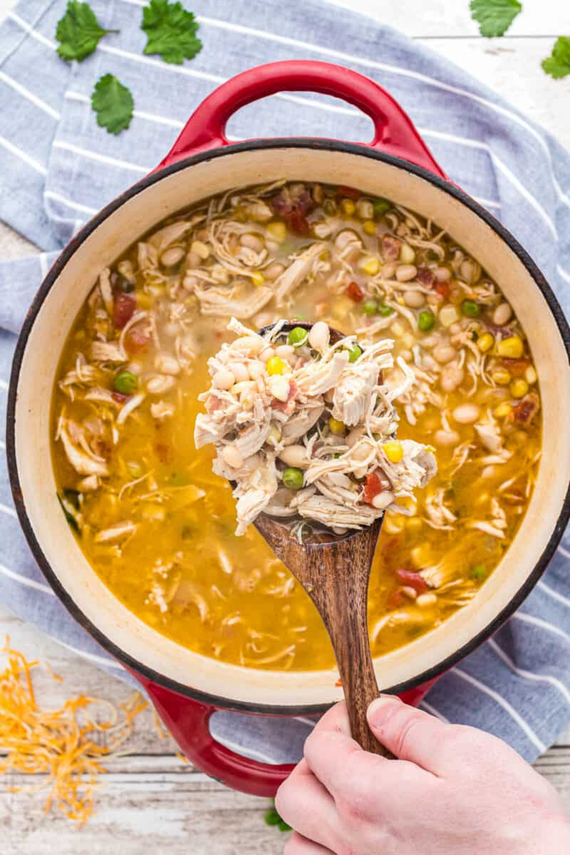 lifting up bacon chicken chili with wooden spoon