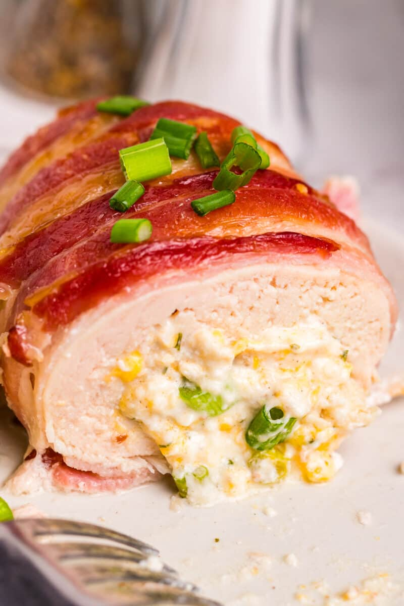 bacon wrapped stuffed chicken on white plate showing inside