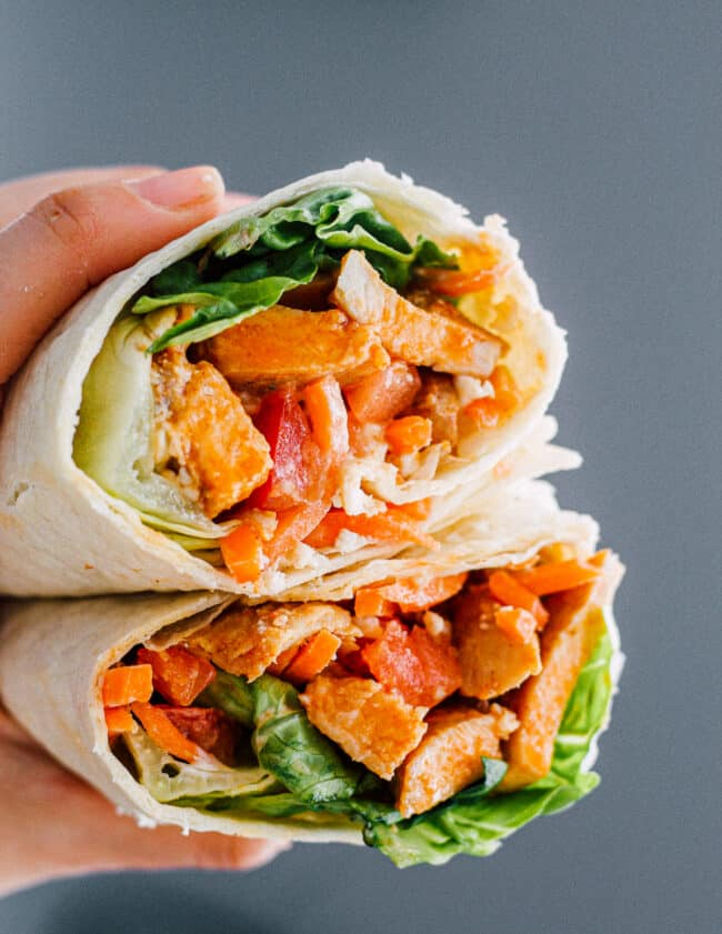 holding up two halves of buffalo chicken wrap