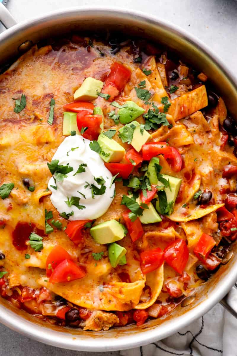 up close chicken enchilada skillet garnished with sour cream, avocado, tomatoes, and cilantro