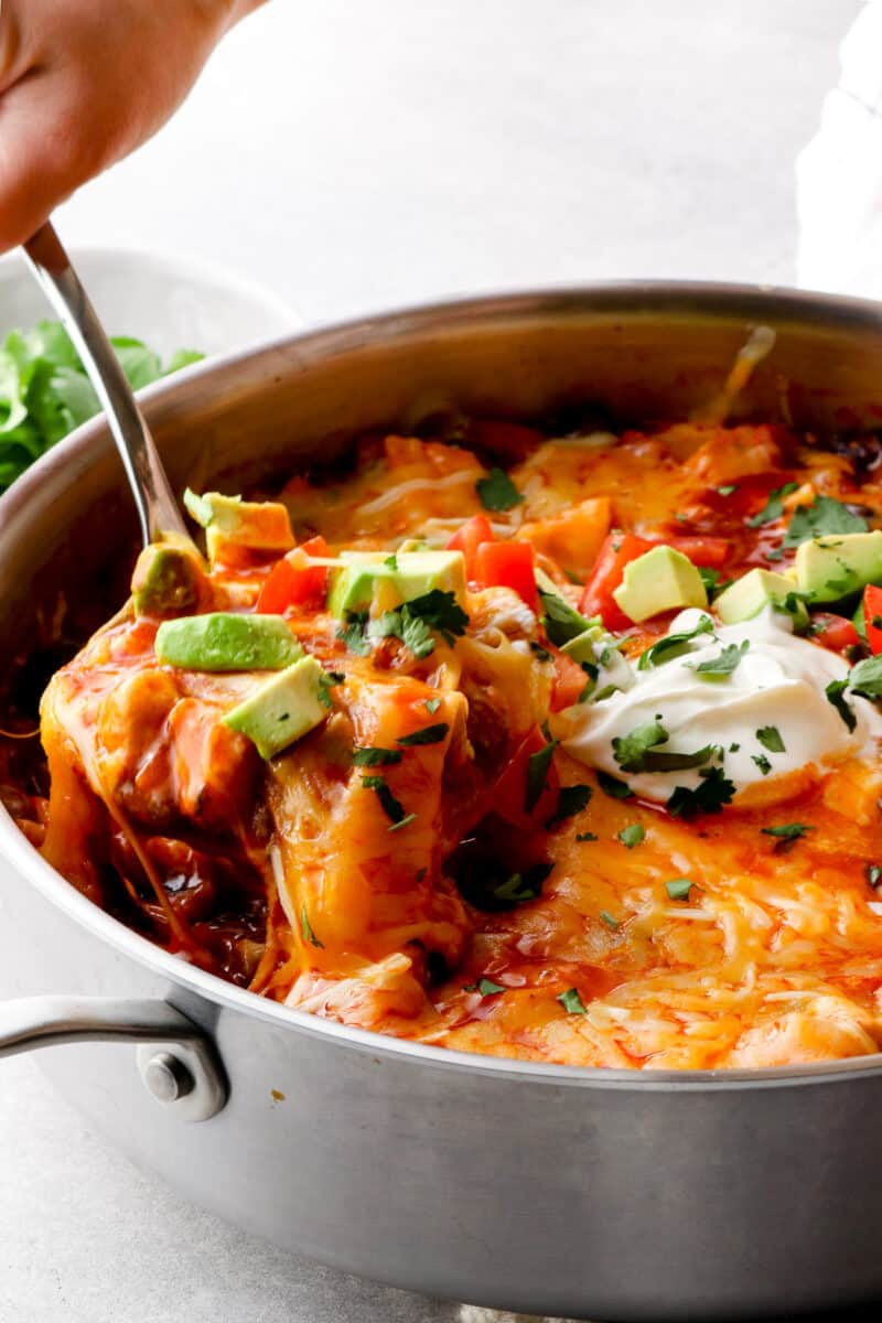 spoon lifting up chicken enchilada skillet