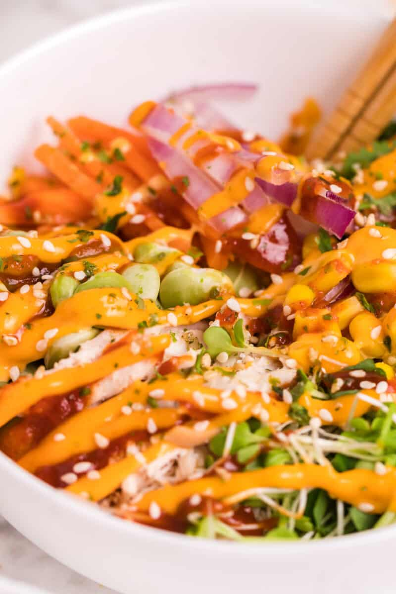 side image of chicken poke bowl drizzled with sriracha mayo in white bowl