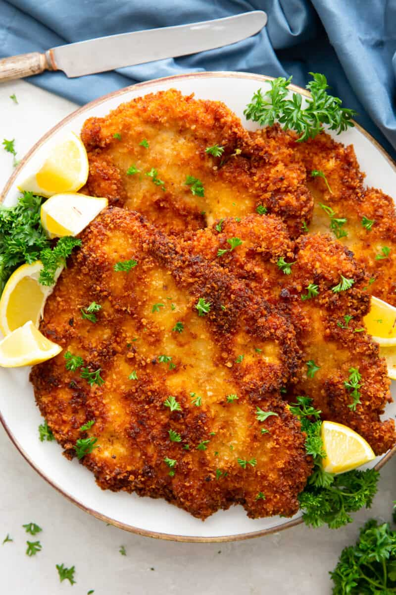 fried chicken schnitzel on plate with lemon wedges