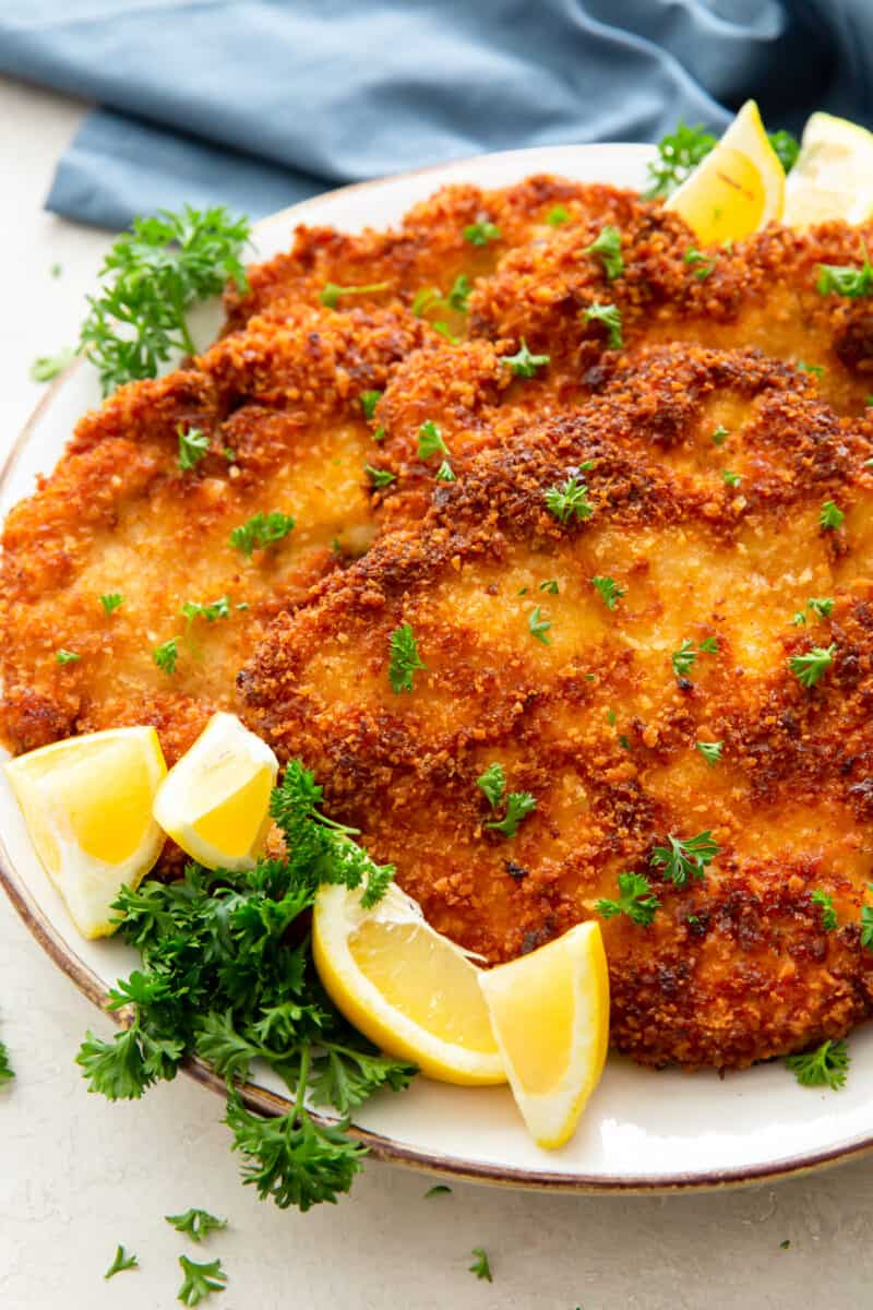 up close fried chicken schnitzel on plate with lemon wedges