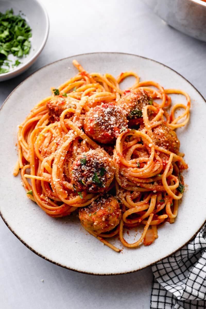 chicken spaghetti and meatballs on white plate