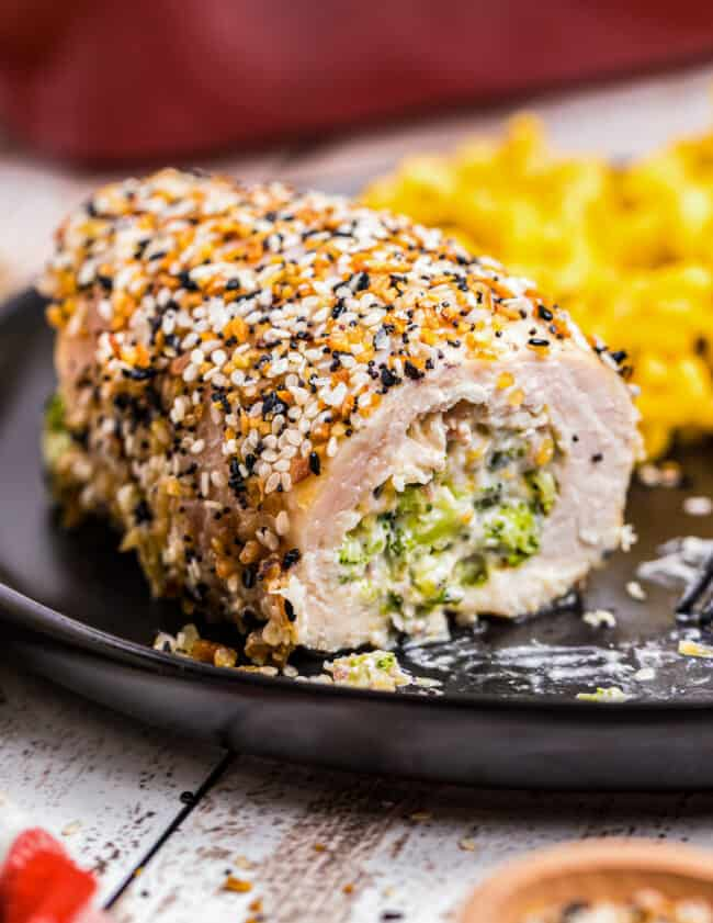 everything stuffed chicken breast on black plate filled with broccoli and cheese