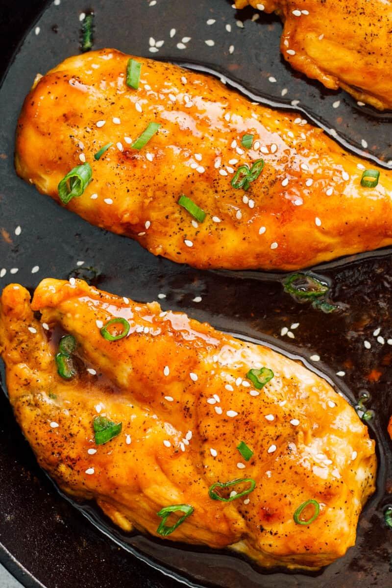 up close honey garlic chicken breasts in skillet