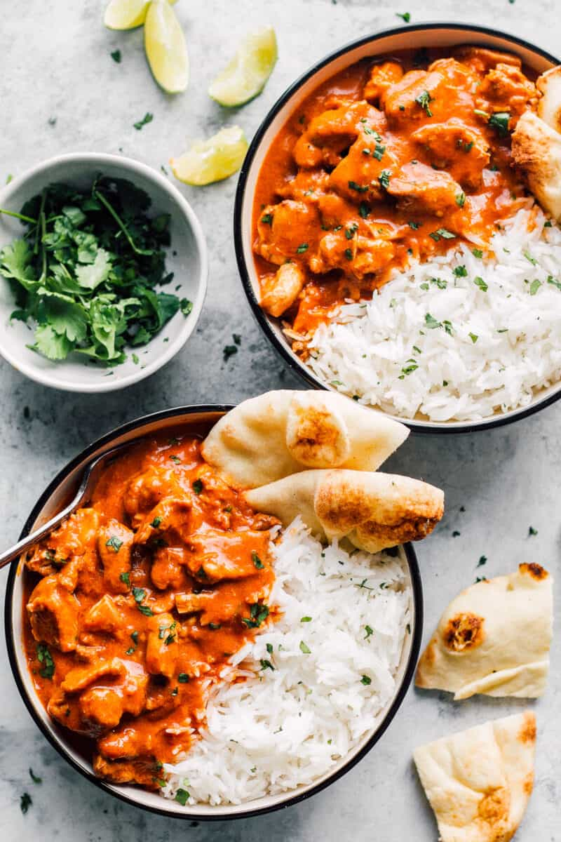 overhead two bowls of instant pot butter chicken with rice and naan