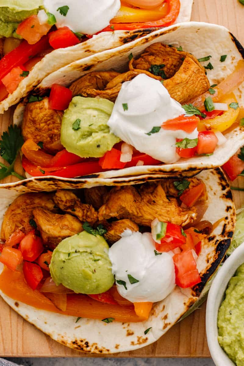 up close instant pot chicken fajitas in tortillas and garnished