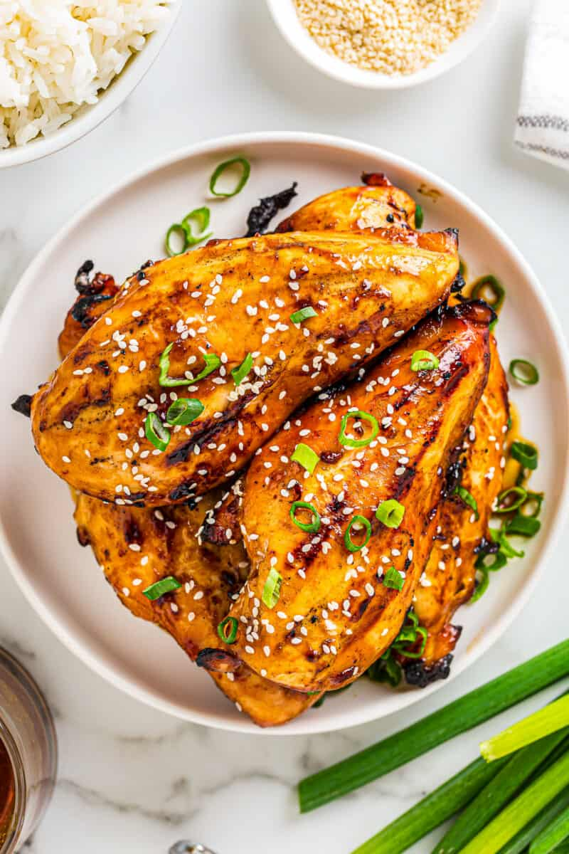 grilled chicken teriyaki breasts with teriyaki marinade on plate