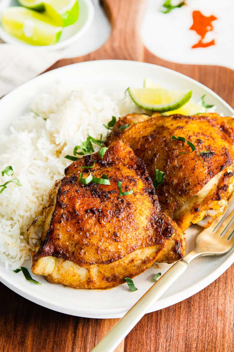 air fryer chili lime chicken thighs on plate with rice
