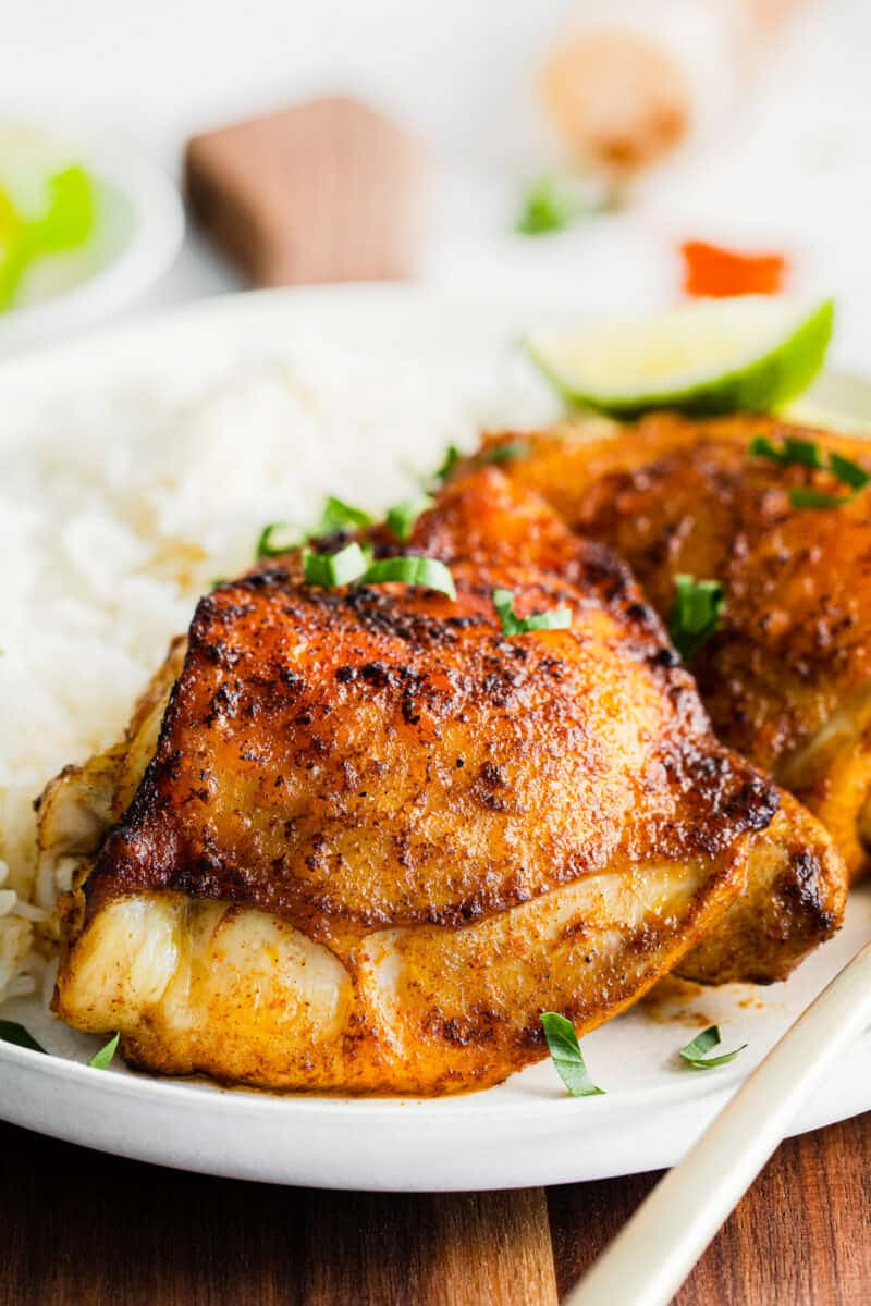 up close crispy air fryer chili lime chicken thighs on plate with rice