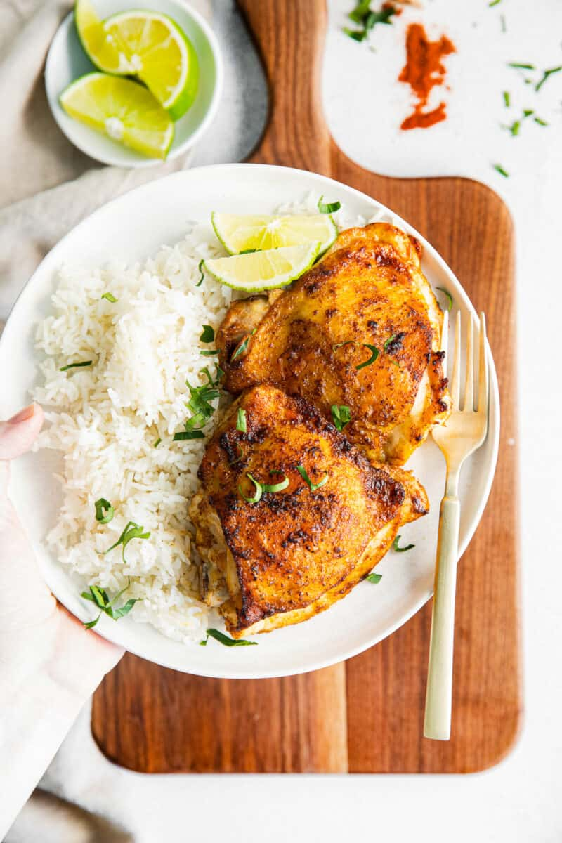 white plate with air fryer chili lime chicken thighs and rice