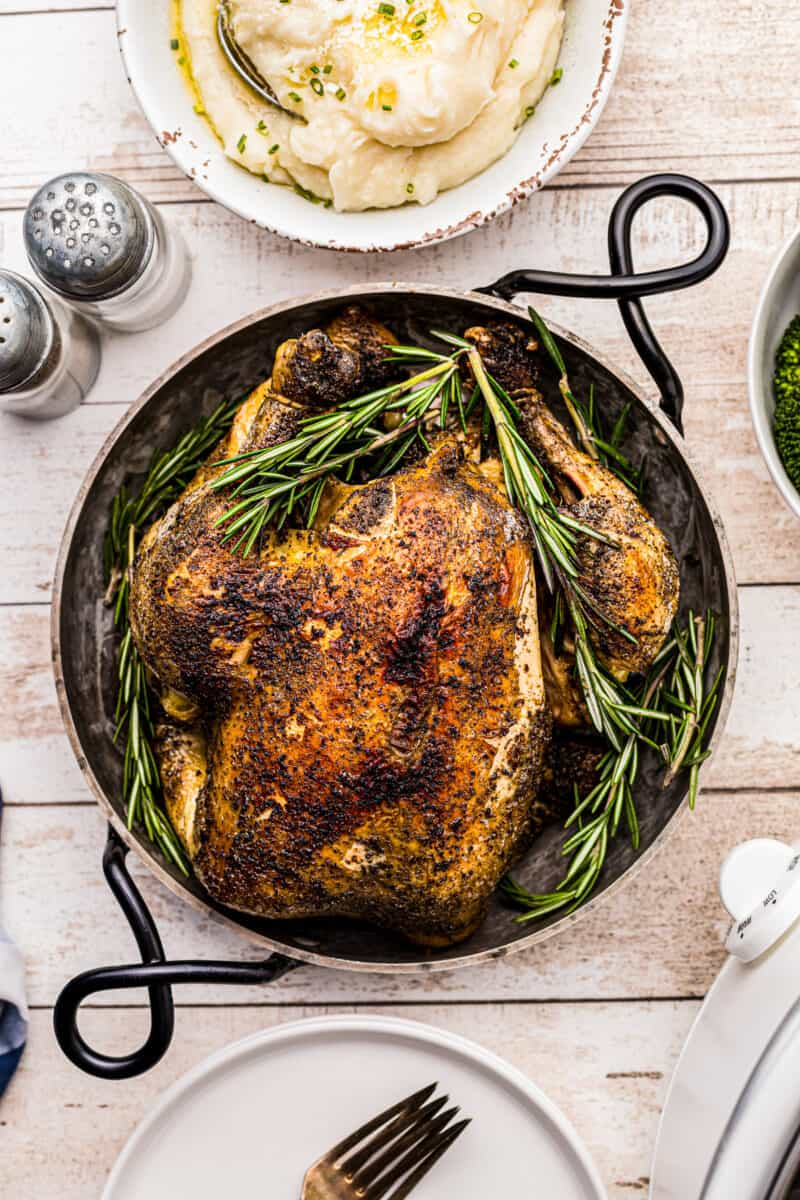 crockpot whole chicken in serving dish with rosemary